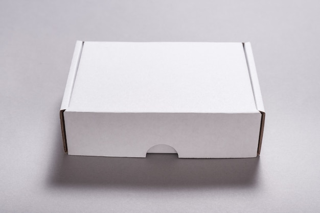 Scatola di cartone di cartone bianco per spedizione postale su superficie grigia