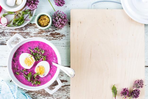 Casseruola bianca con barbabietola estiva fredda, cetriolo e zuppa di uova su un tavolo di legno. vista dall'alto. copia spazio.