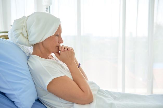 La femmina bianca caucasica senza peli e senza sopracciglia si sente male pregando e aspettando la chemioterapia nella stanza d'ospedale, concetto di mese di consapevolezza del cancro al seno.