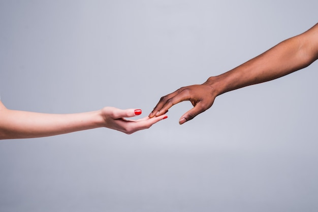 Mano femminile caucasica bianca e mano maschile nera che tengono le dita insieme