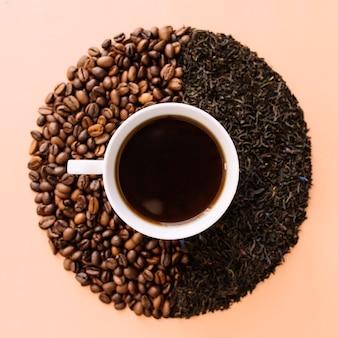 Tazza da caffè in ceramica bianca, chicchi di caffè tostati e foglie di tè essiccate.