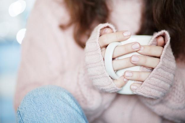 Tazza da caffè in ceramica bianca in mano di donna