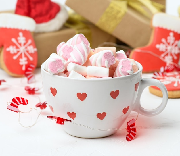 Tazza in ceramica bianca con cacao e marshmallow, dietro una confezione regalo e un giocattolo di natale, da vicino