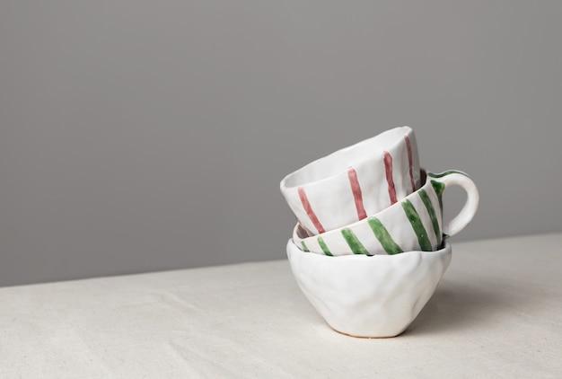 Tazze in ceramica bianca con strisce colorate impilate sul tavolo con tovaglia di lino e sfondo grigio muro. primo piano in ceramica fatta a mano, orizzontale