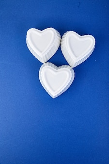 Cuori in ceramica bianca su sfondo blu colore di tendenza. composizione piatta laica. romantico, concetto di san valentino. amore. copia spazio.