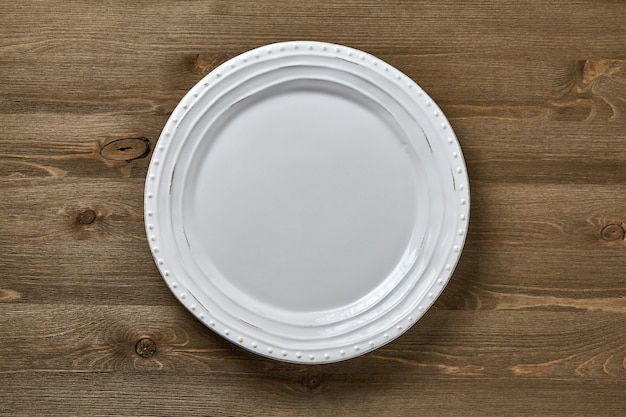Piatto in ceramica bianca su fondo in legno scuro