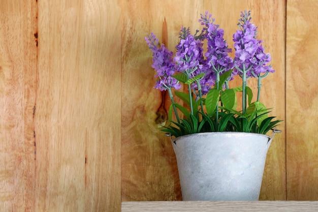 Vaso in ceramica bianca di bouquet di fiori viola sul tavolo di legno con interni e oggetti di parete in legno