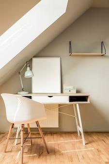 Sedia bianca alla scrivania con lampada e poster in interni luminosi dell'area di lavoro in soffitta. foto reale