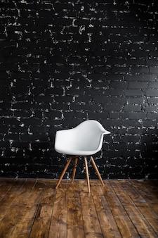 Sedia bianca che sta nella sala sul pavimento di legno marrone sopra il muro di mattoni nero