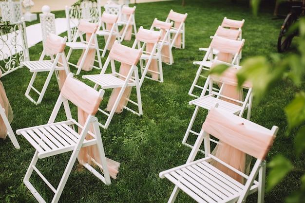 Sedie bianche disposte nell'erba decorazione di nozze estive all'esterno.
