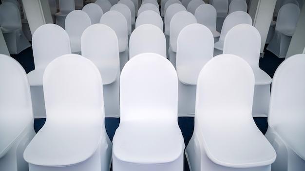 Sedie bianche disposte in una sala per seminari