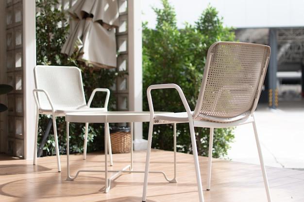 Sedie e tavoli bianchi sono posti sul pavimento in legno.