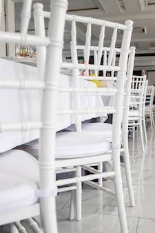 Sedie bianche, tovaglie bianche sui tavoli del ristorante.