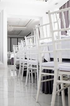 Sedie bianche tovaglie bianche sui tavoli del ristorante