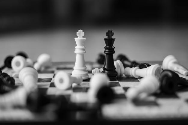 Scacchi bianchi contro scacchi neri su una scacchiera, concetto di strategia aziendale