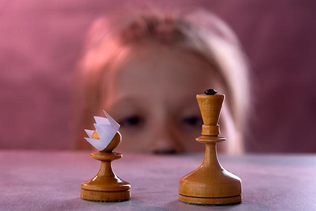 Pedone degli scacchi bianco con una corona di carta in testa contro la regina bianca