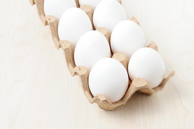 Uova di gallina bianche in un pacchetto a scacchi sul tavolo