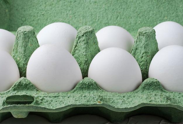 Uova di gallina bianche in un contenitore verde da vicino.