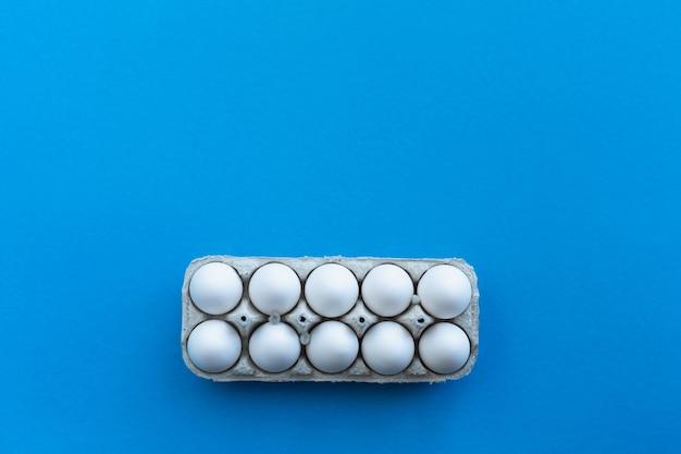 Uova di gallina bianche in una scatola di cartone aperta su sfondo blu