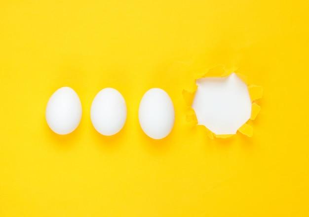 Uova di gallina bianche e carta strappata con foro giallo. vista dall'alto, minimalismo