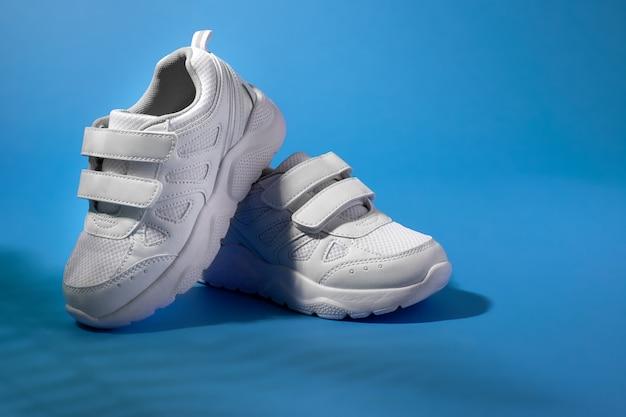 Scarpe da corsa per bambini bianche con chiusure in velcro per calzare facilmente su uno sfondo viola con fer...