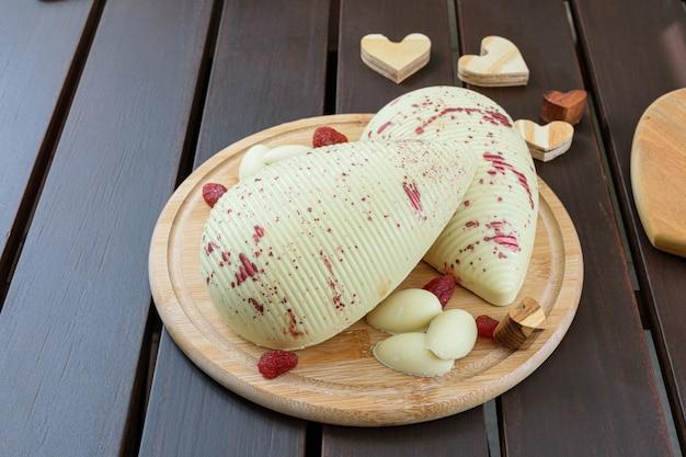 Uovo di pasqua di cioccolato bianco con fragole candite accanto a cuori di legno su un piatto rotondo di legno