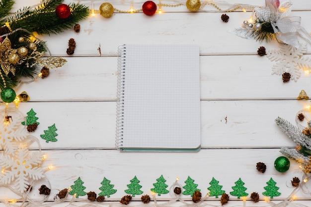 Sfondo di natale bianco decorato con decorazioni festive, lanterne, fiocchi di neve e rami di albero di natale. biglietto di auguri di natale. stagione delle vacanze invernali. felice anno nuovo.