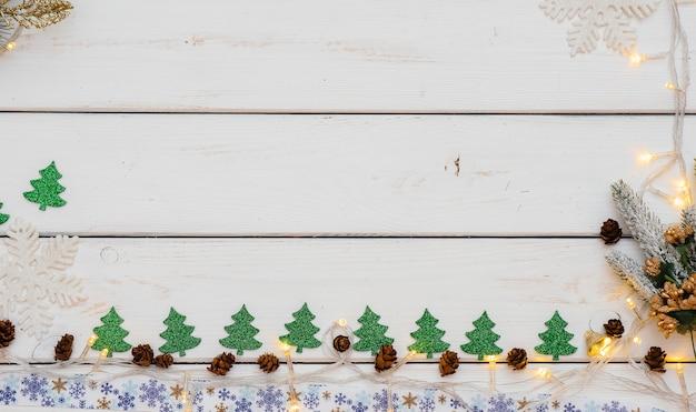 Sfondo di natale bianco decorato con decorazioni festive, lanterne, fiocchi di neve e rami di albero di natale