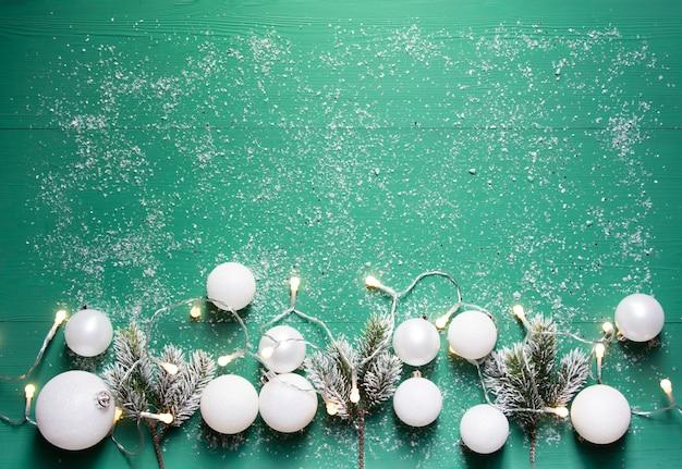 Palle di natale bianche una ghirlanda ardente rami di abete sulla tavola di legno verde con neve