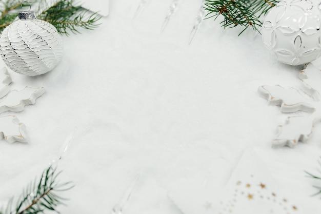 Decorazioni natalizie bianche e rami di abete su neve, sfondo bianco natale, palle di natale bianche.