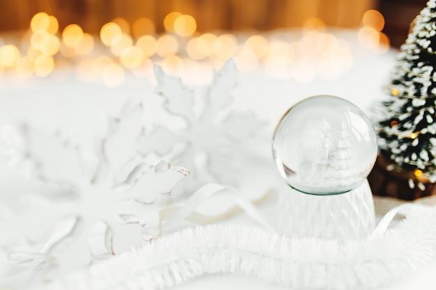 Globo bianco della neve di natale su un tavolo con decorazioni natalizie.