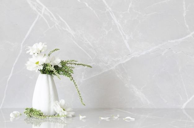 Crisantemi bianchi in vaso a su fondo di marmo grigio