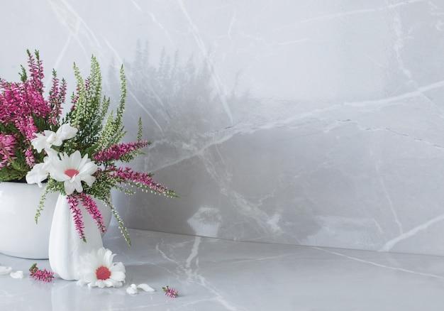 Crisantemi bianchi in vaso ed erica su fondo di marmo grigio