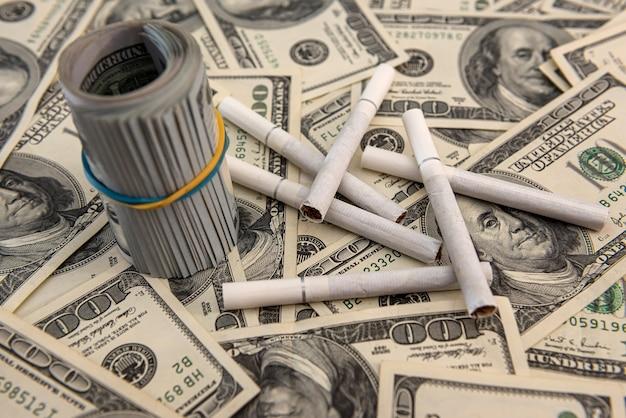 Sigarette bianche che si trovano sulle banconote in dollari. concetto di costo finanziario del fumo.