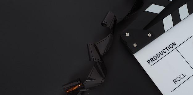 Ciak bianco o ardesia di film e rotolo di pellicola su sfondo nero. utilizzato nel cinema e nell'industria della produzione video.