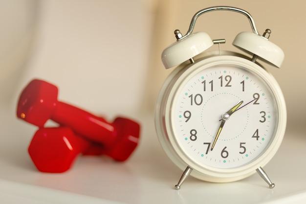 Sveglia classica bianca e manubri rossi sfocati su sfondo bianco tempo per l'esercizio