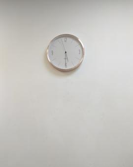 Orologio rotondo classico bianco sul muro grigio copia spazio senza persone design minimalismo interno dell'ufficio