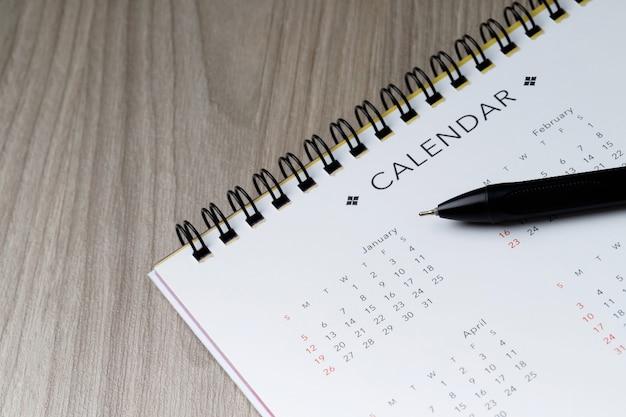 Calendario e penna puliti bianchi su fondo di legno con lo spazio della copia