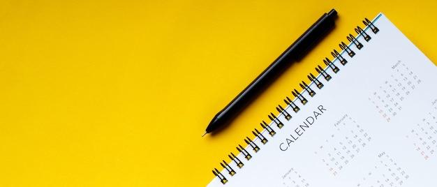 Calendario e penna puliti bianchi su fondo giallo con lo spazio della copia