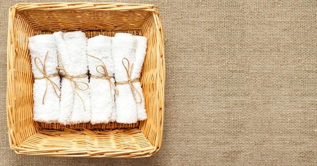 Pila di asciugamani di spugna laminati puliti bianchi nel cesto di vimini sul sacco di lino naturale. avvicinamento. lay piatto. messa a fuoco morbida selettiva. . copia del testo spazio.