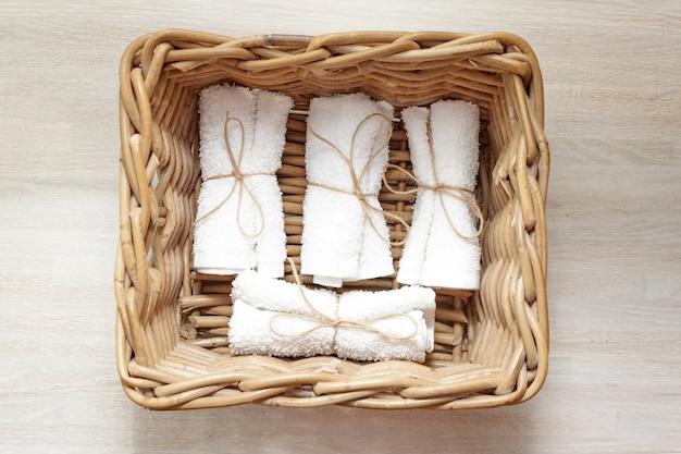 Pila di asciugamani di spugna laminati puliti bianchi nel canestro di vimini su legno naturale. avvicinamento. lay piatto. messa a fuoco morbida selettiva. . copia del testo spazio.