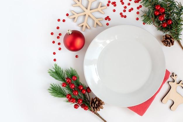 Piatto rotondo bianco pulito, su un tavolo bianco con decorazioni natalizie