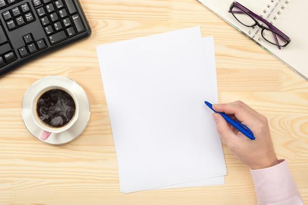 Fogli bianchi puliti per i record, mano tiene la penna, bicchieri da ufficio su un tavolo di legno. lay piatto.