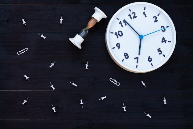 Orologio, clessidra e perni bianchi su un fondo di legno nero. vista dall'alto. copyspace. istruzione o concetto di affari.