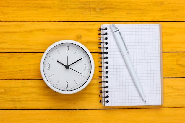 Orologio e taccuino bianchi su superficie di legno gialla. colpo minimalista dello studio. vista dall'alto