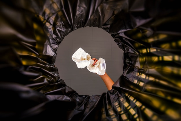 Panno bianco gettato nel sacco della spazzatura