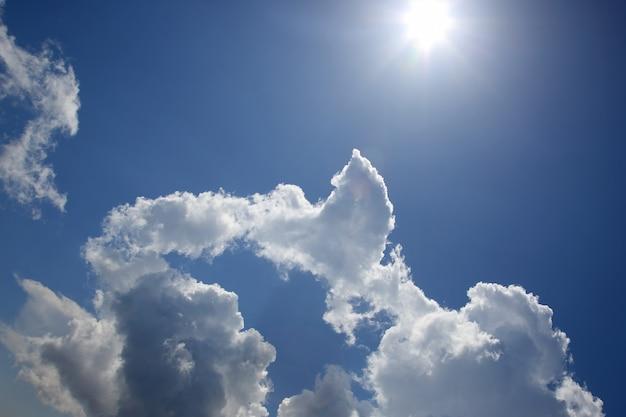 Nuvole bianche nel cielo blu contro il sole splendente