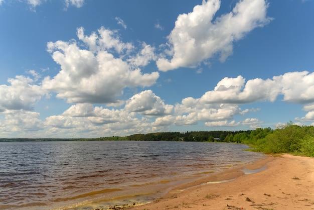 Nuvole bianche nel cielo azzurro sopra il fiume. luminosa giornata estiva in vacanza.