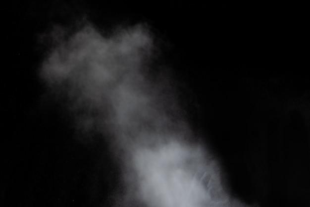 Nuvole bianche di vapore di fumo isolate su sfondo nero. il gas esplode, vortica e danza nello spazio.