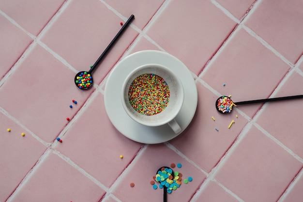 Tazza da caffè bianca piena di granelli di caramelle e un cucchiaio nero su uno sfondo di piastrelle rosa
